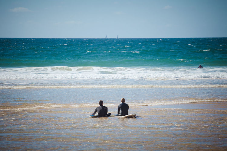 Men sitting on surfboard amidst sea against sky