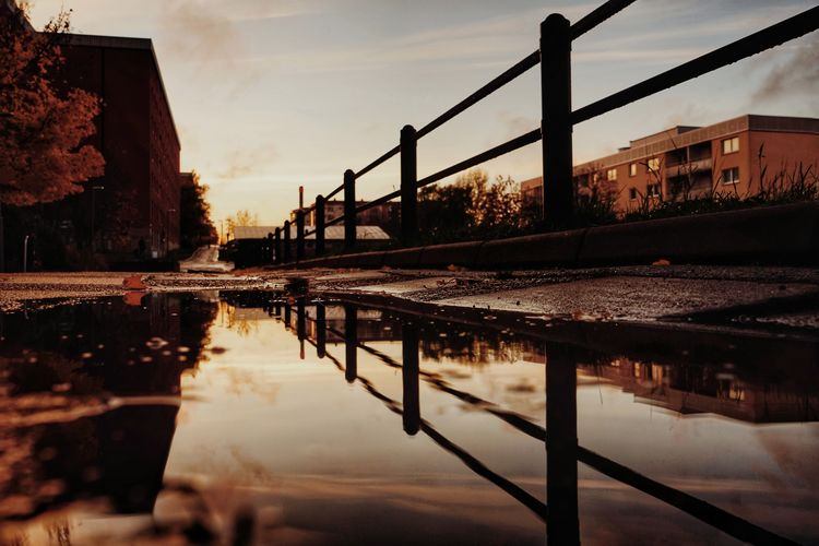 Reflection of buildings in puddle at sunset