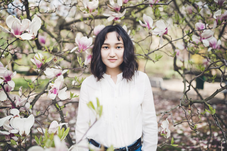 Happy asian young woman under the blooming magnolia tree, smiling