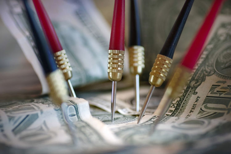 Close-up of paper currency and darts