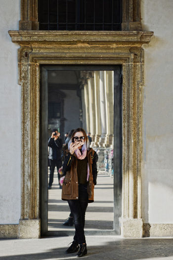 Woman taking selfie while standing at entrance of building