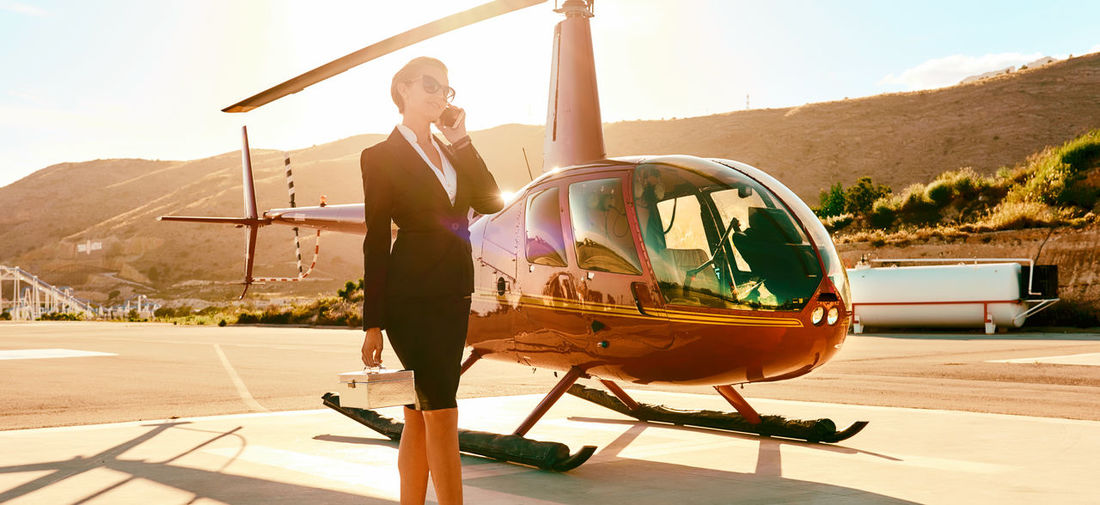 Businesswoman talking on mobile phone while standing by helicopter during sunny day