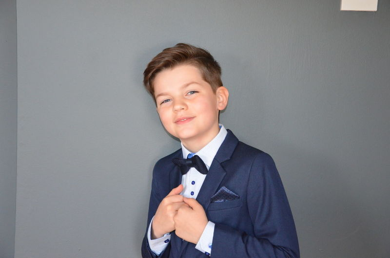 Portrait of boy in full suit standing against gray background