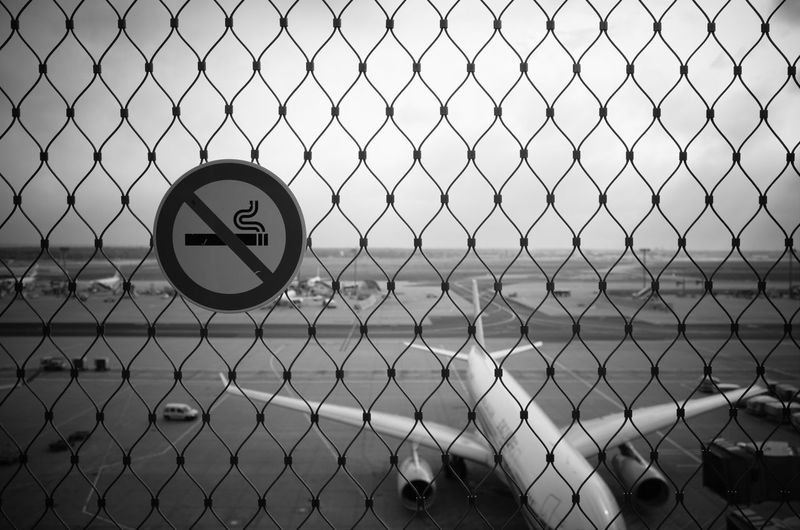 Close-up of signboard on chainlink fence at airport against sky