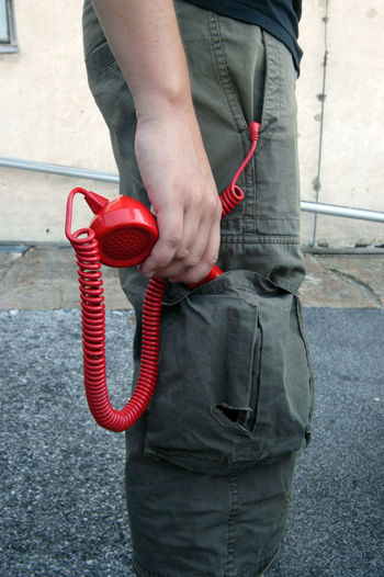 Midsection of man holding red while standing outdoors