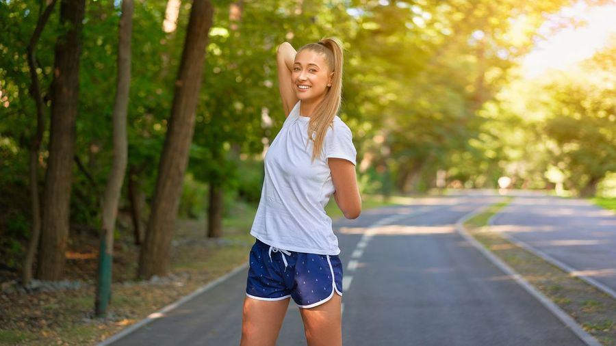 Portrait of smiling young woman standing by road against trees
