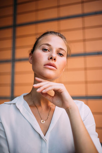 Close-up portrait of businesswoman sitting against wall in office