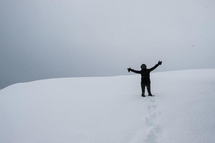 Full length of hand on snow