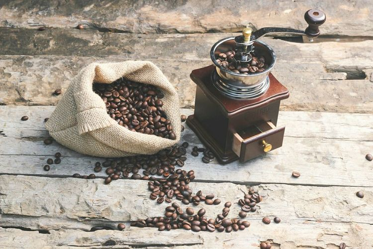 High angle view of coffee beans and grinder on table