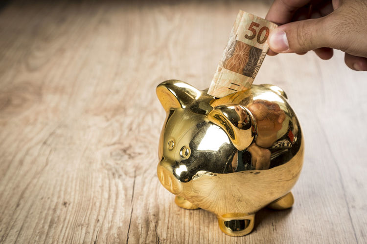 High angle view of person holding paper currency over piggy bank on table
