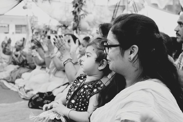 Side view of woman sitting with daughter during event