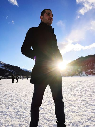 Low angle view of young man with hands in pockets standing on snow covered field against sky