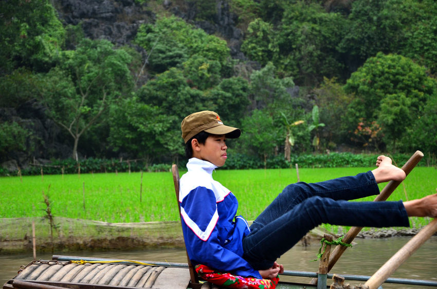 Legs rowing. Vietnam. Aroud The World Casual Clothing Childhood Day Forest Full Length Grass Green Happiness Hard Life In The Forest Legs Rowing Leisure Activity Lifestyles Men Outdoors Perspective Real People Rear View Rice Fields  Ricefield Rowing Rowingboat Sitting Standing Togetherness Travel Traveling Vietnam Vietnam Trip