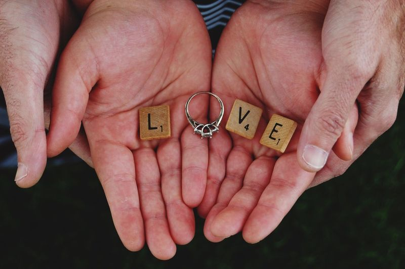 Cropped hands of couple holding wooden blocks with engagement ring making love text