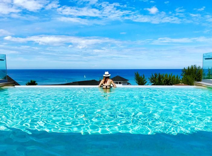 Rear View Of Woman In Infinity Pool Against Cloudy Sky