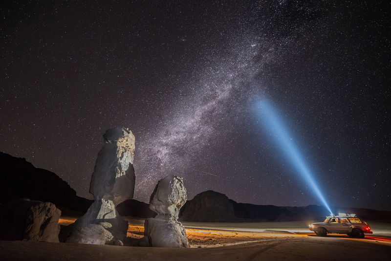 Milky way in Tadrart Algeria Astronomy Beauty In Nature Constellation Desert Flashlight Galaxy Illuminated Milky Way Nature Night One Person Outdoors People Real People Scenics Sculpture Sky Space Space Exploration Star - Space Star Field Statue Transportation Young Adult
