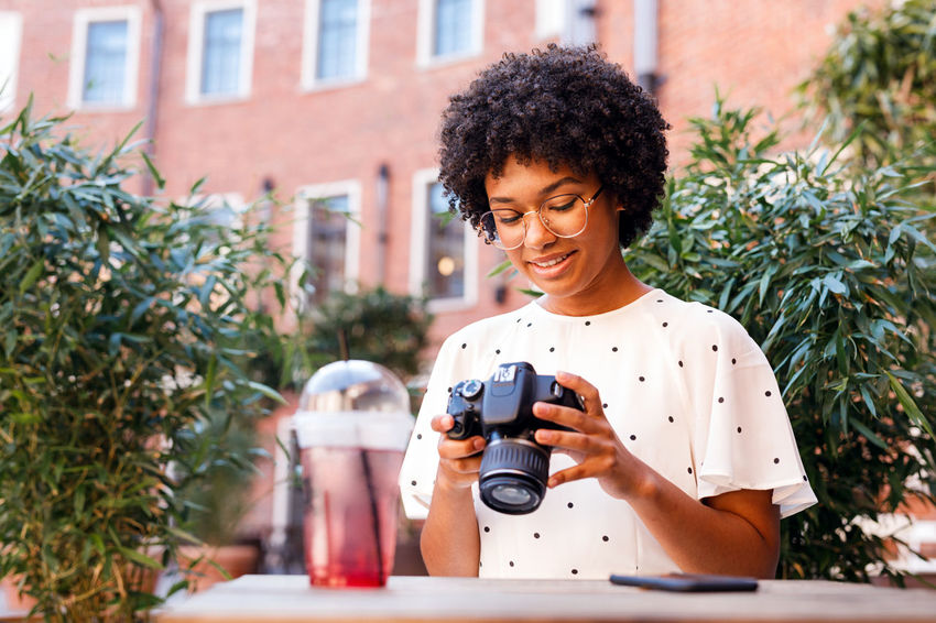 Smiling Portrait One Person Happiness Vlogger Blogger Social Media Girl Woman Selfie Influencer Content Creator  Outdoors Young Lifestyle Cafe Looking At Camera Drink Smartphone Photography Holding Front View Technology Camera - Photographic Equipment