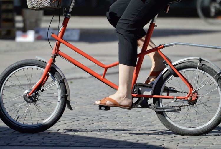 Low section of person riding bicycle on street