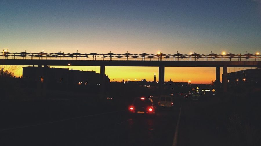 Silhouette bridge against sky during sunset in city