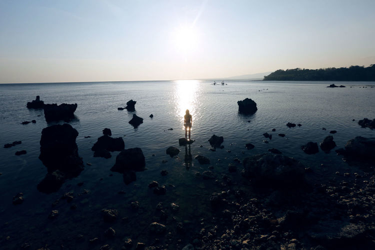 During sunset Sky Reflection Sea Beauty In Nature Sunset Tranquility Tranquil Scene Sun Horizon Horizon Over Water Silhouette Rock - Object Sunlight One Person Woman Ocean Philippines Water Scenics - Nature Nature Rock Solid Clear Sky No People
