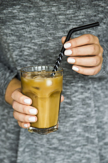 Summer cooling iced coffee drink with milk in female hand Ice Iced Coffee Black Close-up Day Drink Drinking Glass Female Food And Drink Freshness Hand Hold Holding Human Hand Iced Milk One Person Refreshment Straw Summer