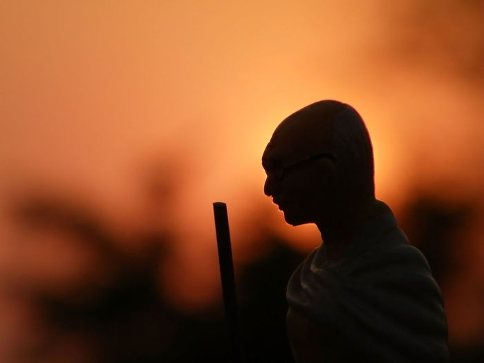 Silhouette man with stick against sky during sunset