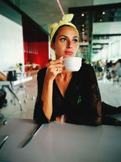 Thoughtful woman with coffee sitting in restaurant