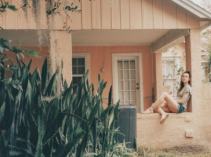 Woman sitting outside house