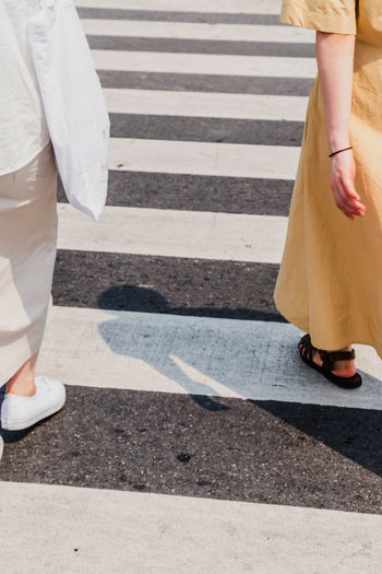 Low section of man and woman walking on crosswalk