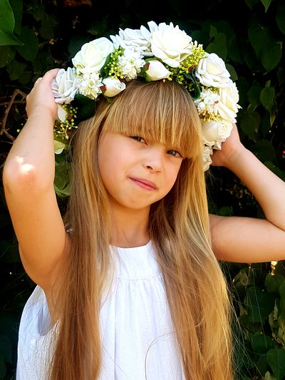 Portrait of girl wearing tiara against plants