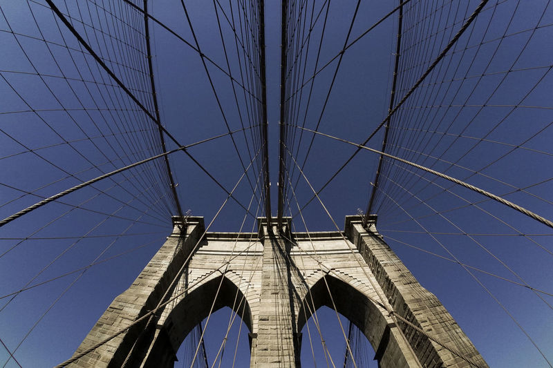 Low angle view of brooklyn bridge against blue sky on sunny day