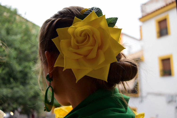 Rear view of woman with yellow rose