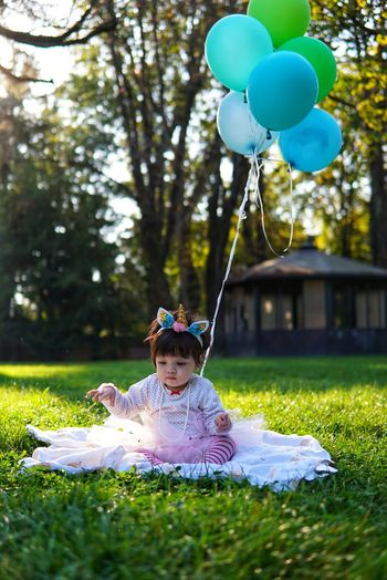 Cute girl with balloons sitting in park