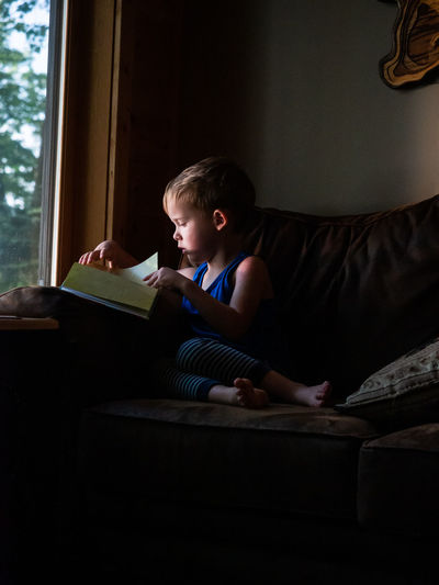 Boy reading book while sitting on sofa at home