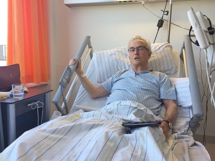 Portrait Of Mature Patient Lying On Bed At Hospital