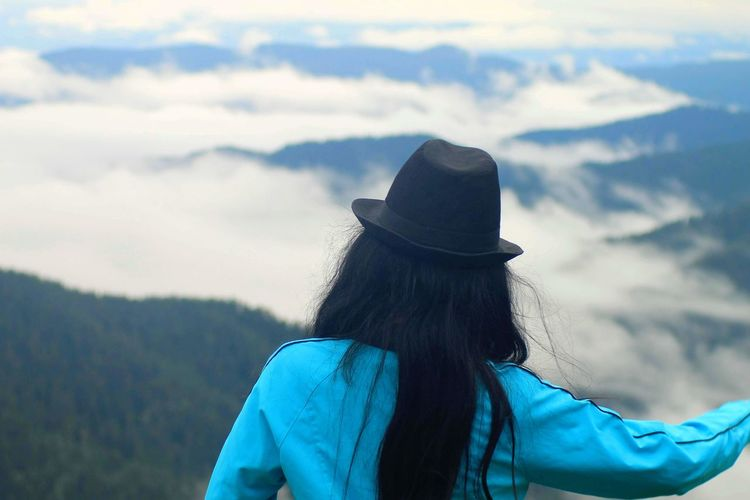 Rear view of woman wearing hat against mountains