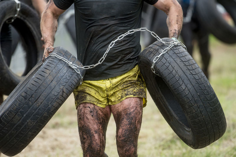 Midsection of man holding tire while exercising outdoors
