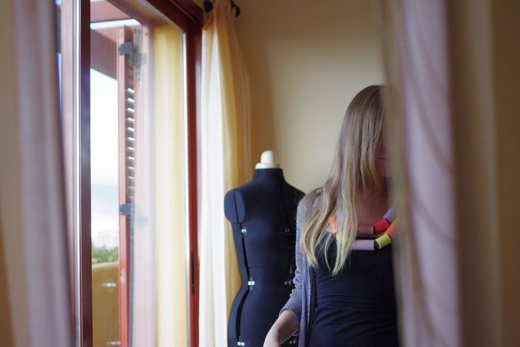 Young woman standing by mannequin at home
