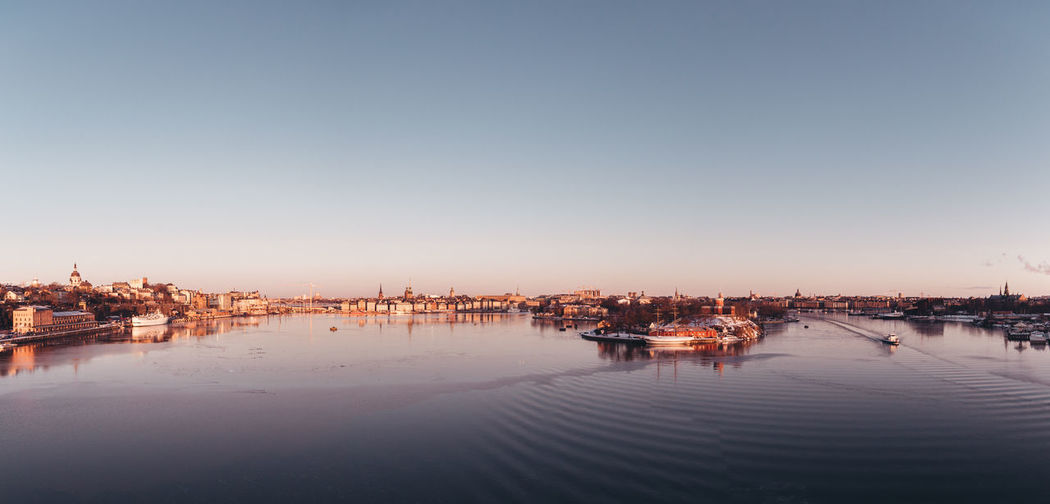 Boats moored in river against clear sky at sunset