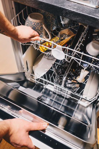 Cropped hands of man holding dishwasher at home
