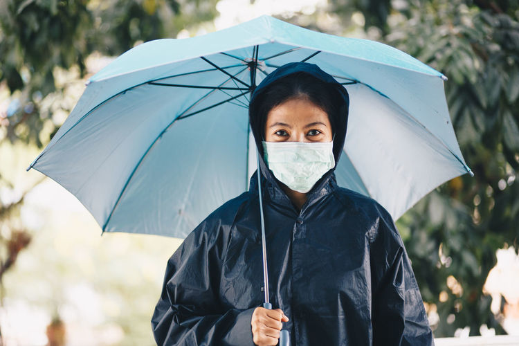Portrait of woman wearing mask and raincoat holding umbrella whole standing outdoors