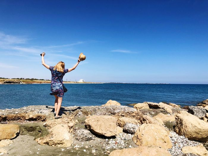 Celebration of life, happy woman on rocks by the sea EyeEm Selects Sea Water Sky Beach Human Arm Land One Person Sunlight Full Length Nature Blue Beauty In Nature Real People Horizon Leisure Activity Standing Limb Arms Raised Arms Outstretched Horizon Over Water The Traveler - 2018 EyeEm Awards