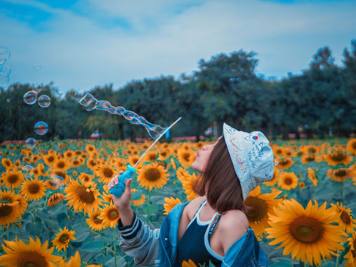 bubble will fly on the sky Plant Flower Flowering Plant Real People Fragility Nature Freshness Lifestyles Vulnerability  Women Beauty In Nature Leisure Activity Growth Day Sky People Child Adult Yellow Sunflower Outdoors Flower Head Hairstyle Young Adult EyeEmNewHere