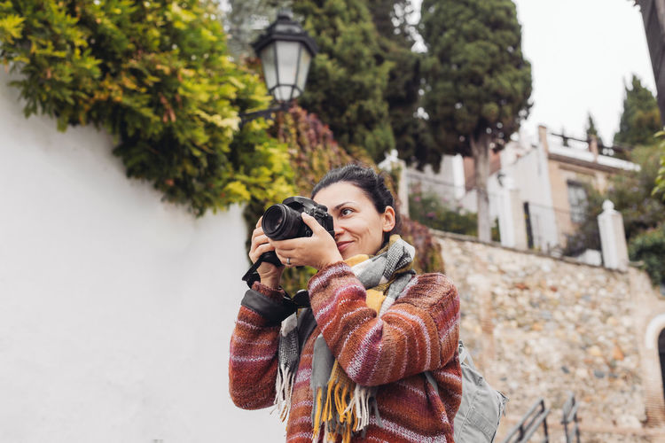 Portrait of woman photographing in winter