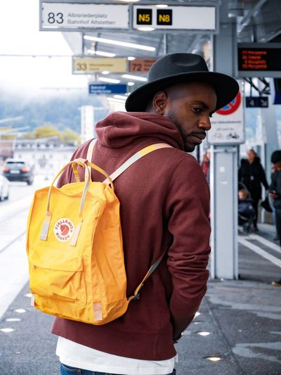 Bring color to your life Fjällräven Bag Pack City One Person Street Architecture Clothing Adult City Life Transportation Standing Side View Bag Day Real People Outdoors Mode Of Transportation City Street Looking Smiling