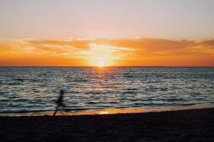 Blurred motion of child running at beach against sky during sunset