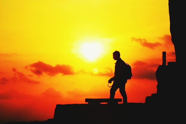 Silhouette man against sky during sunset