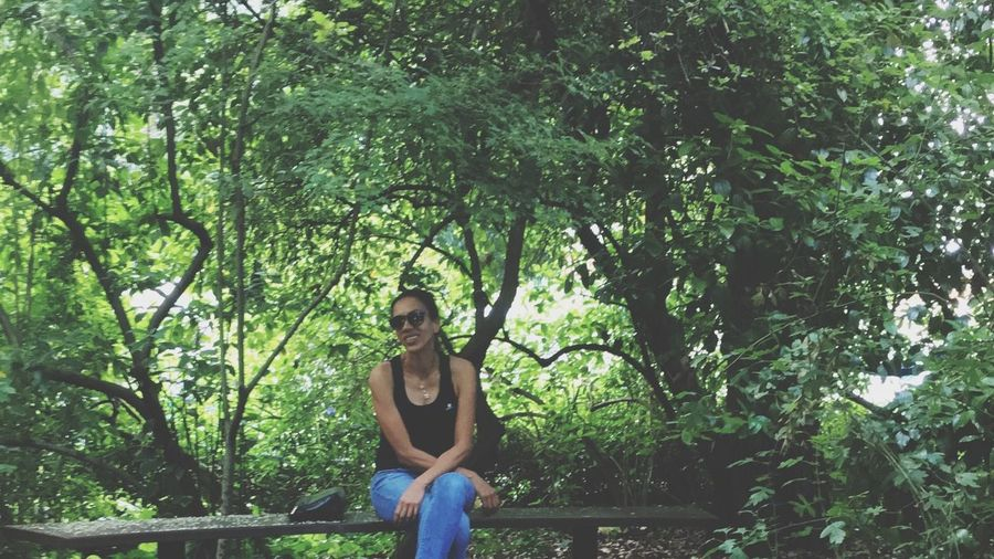 Portrait of woman sitting on bench in forest