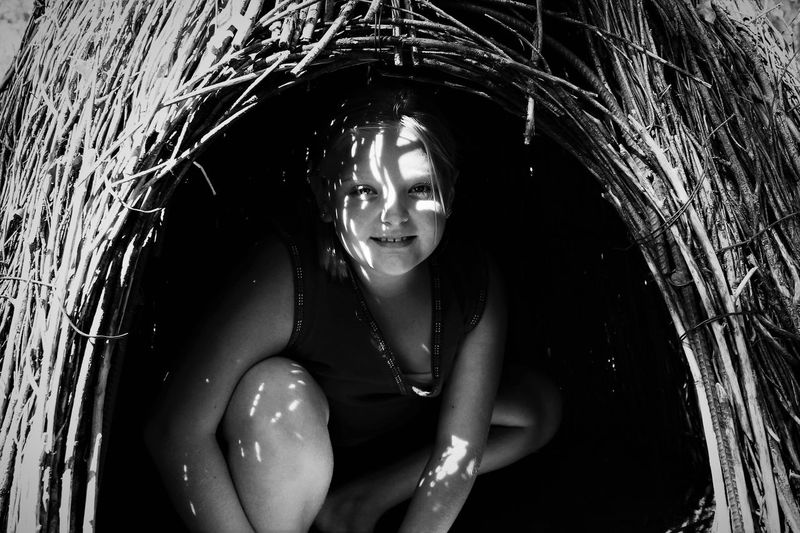 Portrait of smiling girl crouching in hut