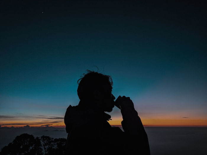 Silhouette man drinking against sea during sunset